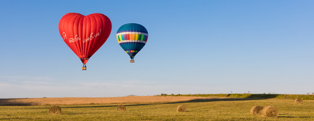 Red heart shaped air ballon with inscription in Russian I love you and colorful air balloons in the sky, banner, toned