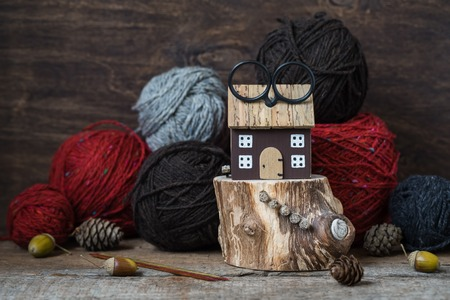 Bright red wool yarn with wooden needles among leaves and acorns, autumn knitting postcard, toned