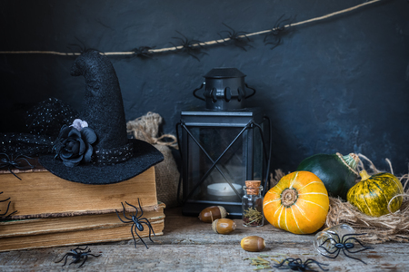 Halloween holiday background with pumpkin, lantern, spiders, old books, black witchhat, toned