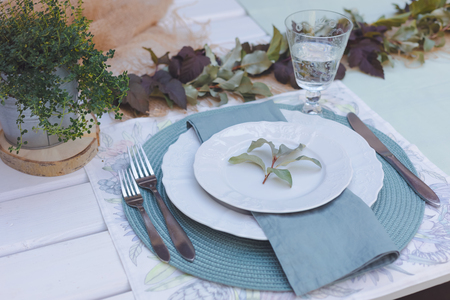 Holiday Summer or early autumn outside table setting with linen napkins and green leaves, toned Banco de Imagens