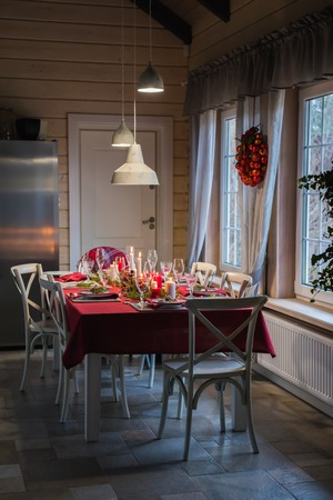 Table served for Christmas dinner, festive setting with decorations, burning candles and fir-tree branches, glasses