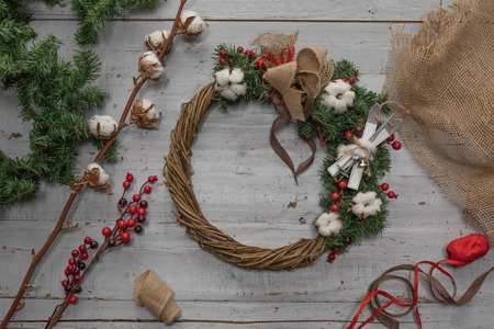 Top view of stages of making Christmas wreath with fir branches and decorative toys on wooden rustic tabletop, toned Standard-Bild