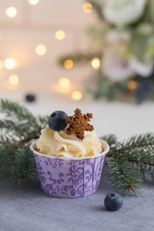 Tasty blueberry muffins with cream on white wooden table, Christmas dessert, fir tree branch, gingerbread cookies