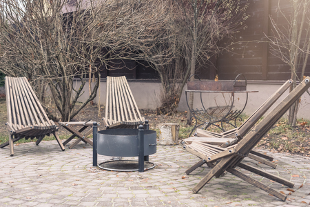 Barbecue and fireplace zone with wooden armchairs, autumn season, toned