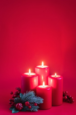 Four red burning advent candles, a green spruce branch on a red background, toned