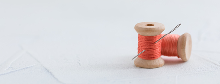 Trendy coral colored threads wooden bobbin for stitching with a needle on a white background