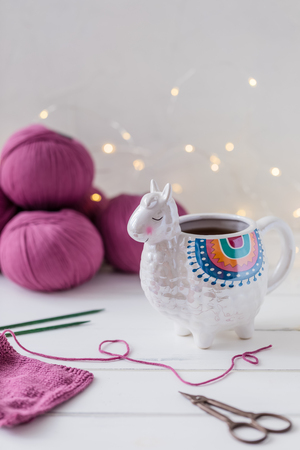 Colorful Llama shaped tea or coffee mug with knitting needles, scissors and wool yarn, hobby postcard concept, 免版税图像