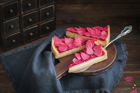 Homemade strawberry tart or pie sliced on wooden plate on the rustic background Stock Photo
