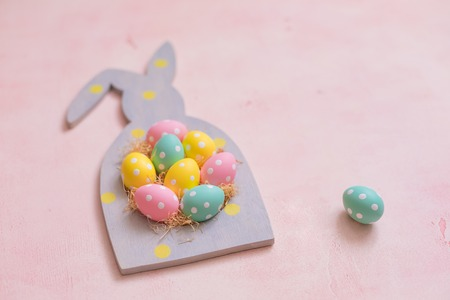Colorful polka dot easter eggs in rabbit-shaped frame on pink concrete background, postcard concept