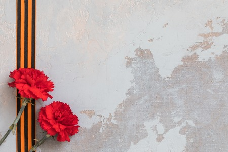 St. George ribbon and red carnation, may 9 Victory Day concept, symbol of the Second World war, concrete background, copy space Banco de Imagens
