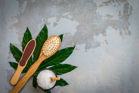 Body spa treatment bamboo brushes with bath salt on green tropical leaf, concrete background