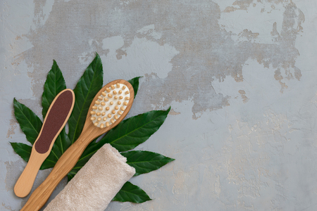 Body spa treatment bamboo brushes with bathtowel on green tropical leaf, concrete background