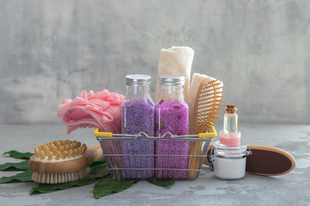 Body spa treatment bamboo brushes with bath salt, cream, oil, towels in a shop basket, concept