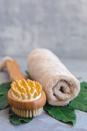 Body spa treatment bamboo brush with bath towel on green tropical leaf, concrete background Stock Photo
