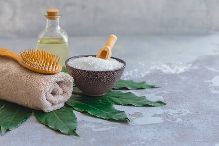 Body hair spa treatment bamboo brush with bath towel and oil on green tropical leaf, concrete background