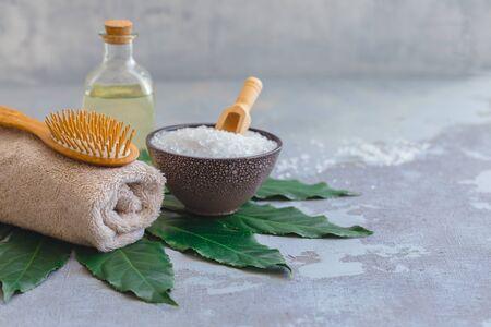Spazzola di bambù per il trattamento dei peli del corpo con asciugamano da bagno e olio su foglia tropicale verde, fondo in cemento Archivio Fotografico