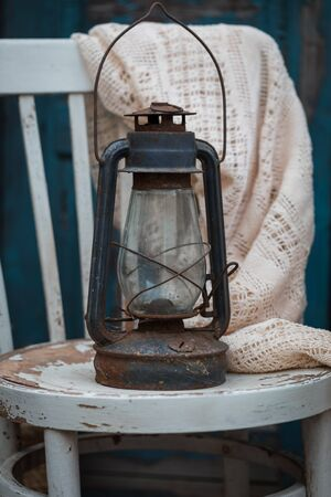 Antique oil lamp on the rustic white chair, toned