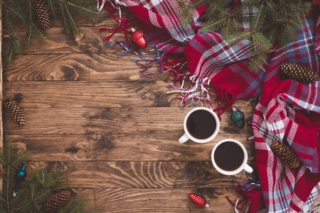 Hot Christmas Beverage Chocolate or Coffee in cups with Sparkles, Fir Tree Branches, toys, plaid on Wooden Background. Winter Time Top View, toned