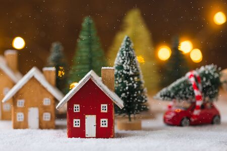 Miniature wooden houses over blurred Christmas decoration background, property real estate investment greetings concept