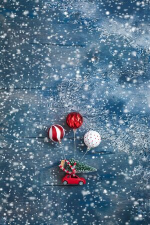 Miniature toy red car with fir tree and balls like air balloons on the snowy background, postcard concept, toned