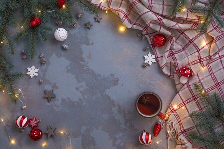 Christmas tea cup with cinnamon, cookies, Fir Tree Branches, toys, plaid on concrete linen background. Winter Time Top View, toned