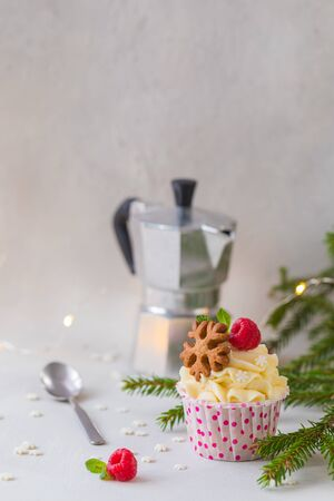 Christmas cupcakes or muffins with cream and raspberry, over the fir tree branches background, toned