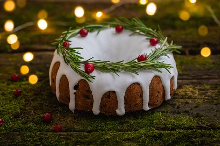 Traditional homemade Christmas fruit cake on the natural wooden background with moss, decorated by cranberries and rosemary