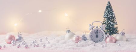 Pink and White glass Christmas balls with an alarm clock on a snowflake background, toned, postcard concept