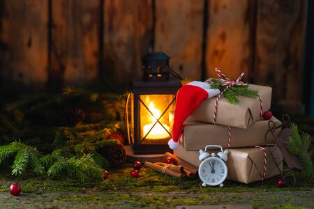 New Year Christmas composition with pile of presents wrapped in craft paper on natural moss background with alarm-clock, Santa Claus hat and sledge, and fir-tree branches, zero waste holiday concept Stock fotó