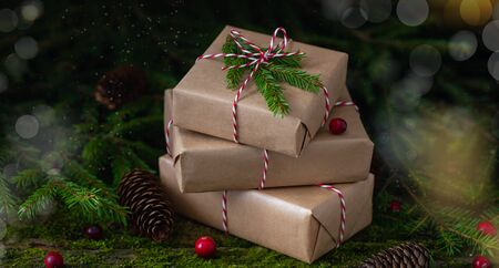 New Year Christmas composition with a pile of presents wrapped in craft paper on natural moss background with fresh cranberries, cones and fir-tree branches, zero waste holiday concept Stock fotó