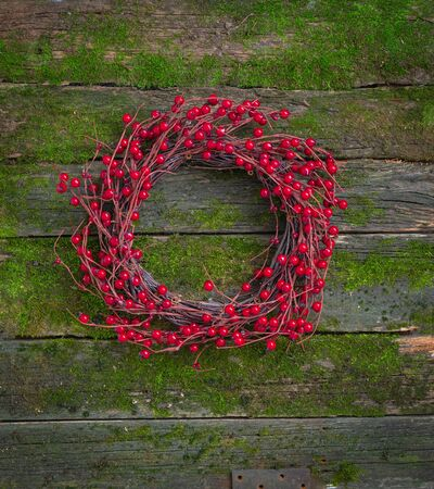 Cristmas red berries wreath on the natural moss wooden background, toned