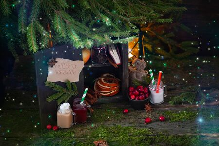 Christmas magic wooden cupboard with holiday drinks and ingredients,cinnamon, glass mugs, cranberries, dried oranges, branches of fir-tree, lantern, postcard concept