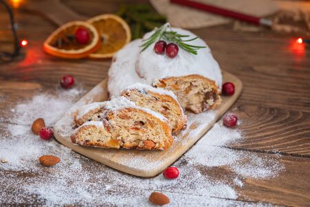 Traditional Christmas German cake Stollen with raisins and nuts on the wooden background with lights