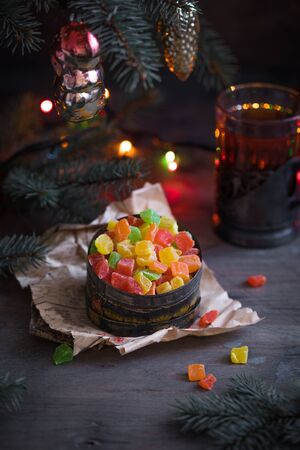 Vintage USSR christmas box with candied fruits and peels on the old newspaper with old toys on fir tree branches and sparkling garland and cup of tea