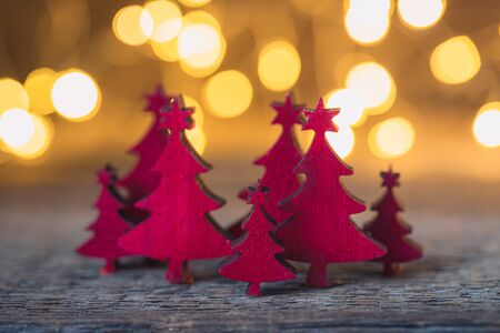 Christmas vintage red wooden firtrees with garland lights background, holiday concept, toned Reklamní fotografie