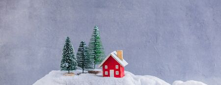 Miniature red wooden house over blurred Christmas decoration background, property real estate investment greetings concept