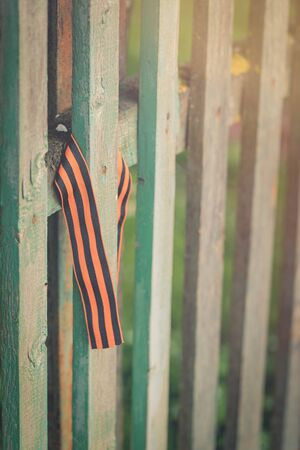 St George's ribbon tied to an old fence, Second World War Victory Day concept