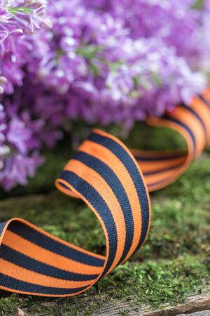 St. George ribbon on natural moss wooden background, symbol of Victory Day May 9, toned