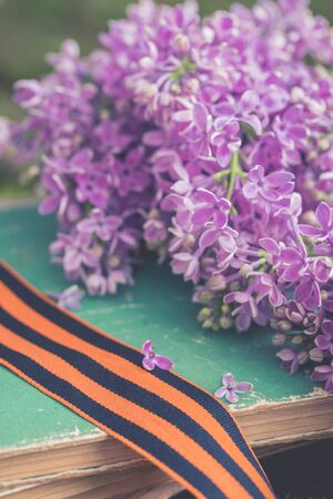 St. George ribbon on old books background with fresh lilac branch, symbol of Victory Day May 9, toned 스톡 콘텐츠