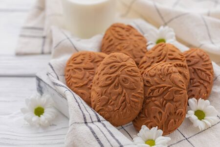 Easter egg shaped ginger cookies on the kitchen towel background with glass of milk and diasy flowers
