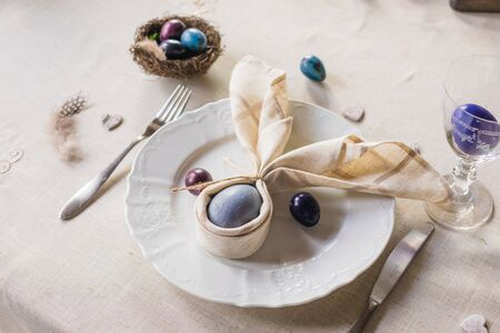 Easter festive spring table setting decoration, bunny ears shaped napkins, dyed hen's and quail eggs, feathers, wooden hearts, family dinner or breakfast concept