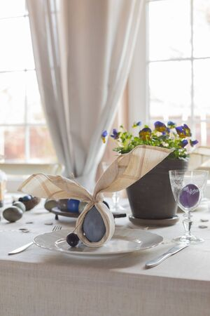 Easter festive spring table setting decoration, bunny ears shaped napkins, dyed hens and quail eggs, cakes, violets potted, feathers, family dinner or breakfast concept, banner