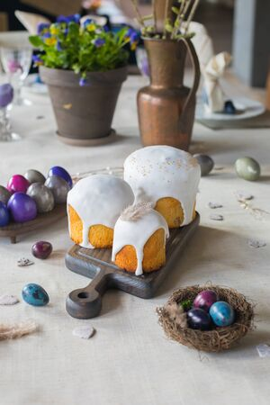 Naturally dyed Easter quail eggs in nest, Easter cakes, fresh violets potted, wooden hearts background, retro styled spring holiday greeting postcard concept 免版税图像