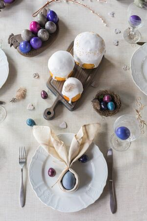 Easter festive spring table setting decoration, bunny ears shaped napkins, dyed hens and quail eggs, cakes, feathers, family dinner or breakfast concept