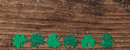 St Patrick day background with shamrock clover leaf on wood, Irish festival symbol, toned, with fairy dust texture, copyspace