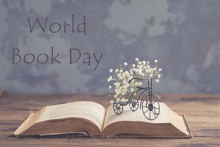 Old book, miniature iron bicycle with white fresh flowers on wooden background, World Book Day concept, toned vintage