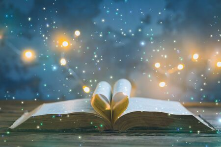 Old opened book, heart shaped paper sheets, dark background with stars and lights, World Book Day, Teachers Knowledge Day, astrology, astronomy and mystery concept, toned vintage Stock Photo