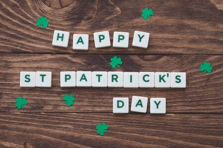 Letters Happy St.Patrick's Day on wooden background, greeting card, paper shamrocks decoration