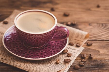 Nice purple cup of coffee with beans on newspaper background, selective focus, toned vintage 版權商用圖片