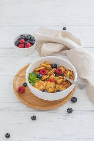 Breakfast white bowl with tiny pancake cereal with blueberries, raspberries and mint on wooden background
